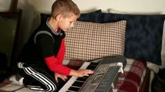 Young boy playing with an electric keyboard Stock Footage