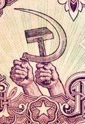 Hands holding hammer and sickle - stock photo