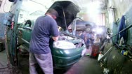 Stock Video Footage of Worker of car-care center collects car suspension bracket
