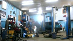 Car stand in car-care center garage near mechanics Stock Footage