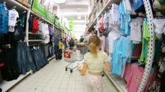 Women go along rack with children clothes in Ashan hypermarket Stock Footage