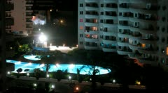 People swim in pool near housing estate in evening, time lapse Stock Footage