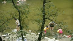 People swimming in lake,mother teach children to swim,dense forests. Stock Footage