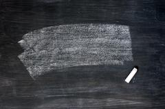 smudged blackboard background with chalk and copy space - stock photo