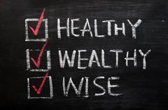 Being healthy, wealthy and wise written with chalk on a blackboard Stock Photos