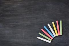 colorful chalk on a blank smudged blackboard - stock photo