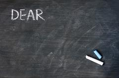 smudged blackboard background with chalk and the word dear - stock photo