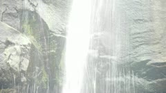 Waterfall on cliffs in mountains,flowing into pond lake. Stock Footage