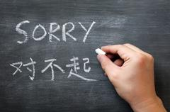 sorry - word written on a smudged blackboard - stock photo