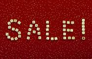 "Stock Photo of word ""sale"" of beads on a red velvet with sequins"