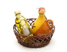 Bottle and jar of virgin olive oil in basket Stock Photos