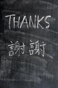 Thanks - word written on a blackboard with a chinese version Stock Photos