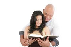 Attractive couple reading the bible Stock Photos
