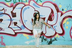 Girl against grafitti wall Stock Photos