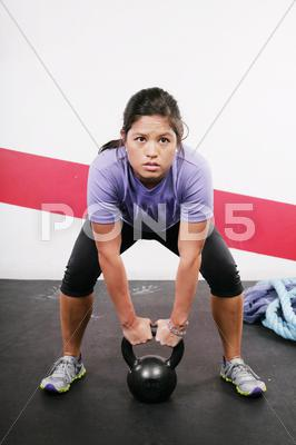 Stock photo of portrait of young woman having a short break in her kettlebell crossfit worko