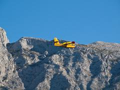 Fire fighter airplane flying near mountain - stock photo