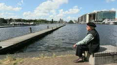 Netherlands Amsterdam canal pier man in beret Stock Footage