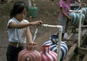 Stock Photo of guatemala girls drawing water from standpipe at