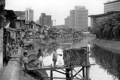 Contrasts slum next to downtown offices jakarta Stock Photos