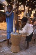 Mozambique children kids pounding grain people Stock Photos