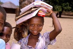 Children kids girl carrying school books people Stock Photos