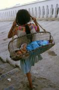 Mexico hispanic girl carrying baby sister in Stock Photos