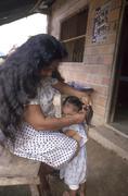 mother grooming child kid hair sepecho alto beni - stock photo
