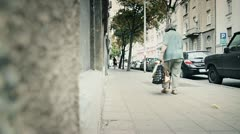 Lonely old woman walking down the street Stock Footage