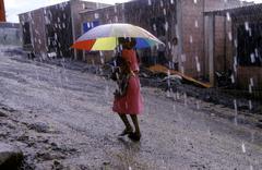 Guatemala woman female walking in the rain city Stock Photos
