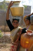india water girls carrying pots from well in - stock photo