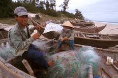 vietnam fishing fishermen mending nets binh - stock photo