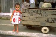 Baby girl child kid stands next junk cart gaze Stock Photos