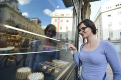 woman in front of sweet store window - stock photo
