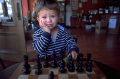 hand child kid face young boy playing chess - stock photo