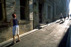 peole strolling through brightly lit narrow - stock photo