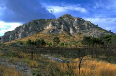 rocky hillside bare trees shrubs clouds avignon - stock photo