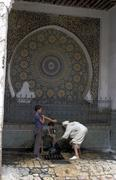 Morocco water fountain fes mosaic wash people Stock Photos