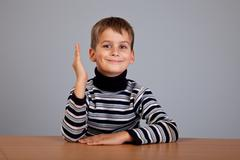 cheerful schoolboy ready to answer question - stock photo