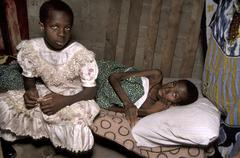 Tanzania mother dying of aids her daughter sits Stock Photos