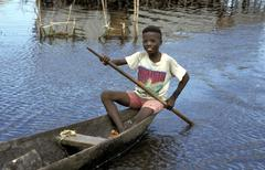 Benin boy paddling pirogue ganvie the village on Stock Photos