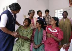 Stock Photo of india sisters leela and achama greeting patients