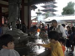 Japan visitors drinking sacred water at asakusa Stock Photos