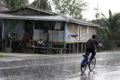 Thailand boy riding bicycle ion the rain pattani Stock Photos