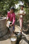 cambodia woman female taking water from well - stock photo