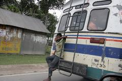 Bangladesh boy hanging from bus use embargoed in Stock Photos