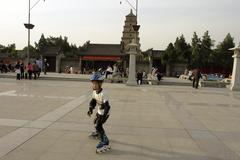 China boy roller blading in front of little Stock Photos