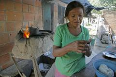 honduras woman female making tortillas the slum - stock photo