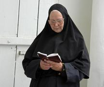 russia nun reading scripture pechersky the caves - stock photo