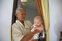 indonesia bab with gradmother tsunami survivors - stock photo