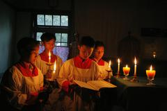 Myanmar boys reciting gospel in candle light at Stock Photos